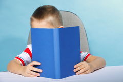 child-boy-kid-reading-book-blue-young-background-holding-open-34023413