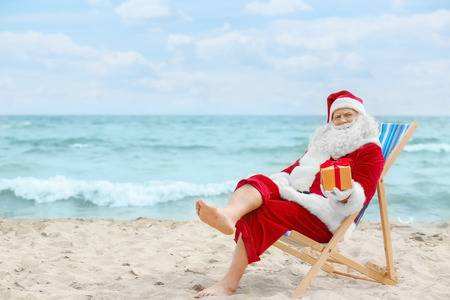 98713664-authentic-santa-claus-with-gift-box-in-deck-chair-on-beach